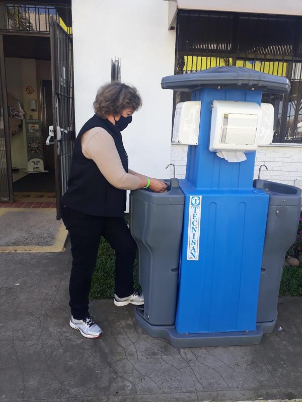 Secretária Covatti experimenta um dispenser de álcool gel e lavatório de mãos  Foto Divulgação SEAPDR